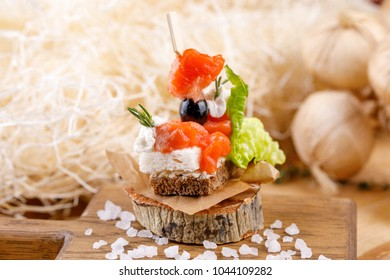 Canape with salmon on a cut wood. Rustic. Close-up.