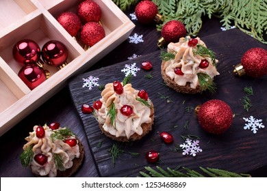 Canape shaped as a Christmas tree with pate garnished with pomegranate and dill surrounded by Christmas decorations