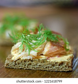 Canape with smoked Arctic char, paprika cream cheese and dill on rye bread. Delicious starter or cocktail snack. Close up square shape image with copy space.