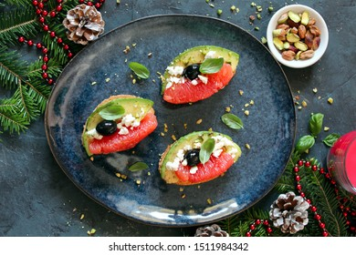 Canapes with avocado, feta cheese, grapefruits, pistachio and basil. Top view with copy space. Healthy food concept for Christmas or New Years.