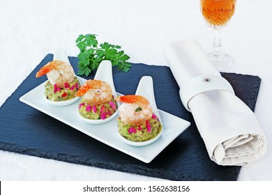 Canapes with avocado spread and shrimp served on white porcelain appetizer tasting spoon over black slate platter.