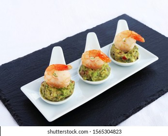 Canapes with avocado spread and shrimp served on white porcelain appetizer tasting spoon over black slate tray.