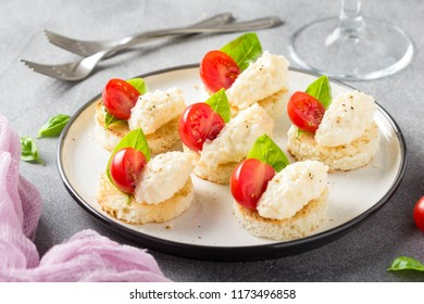 Canapes with cheese mousse, cherry tomato and basil, a small sandwich on crispy toast with cheese and garlic dumplings. Delicious appetizer, wine snack