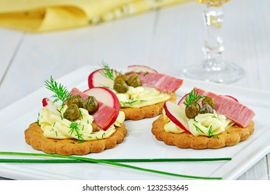Canapes with cream cheese, ham, red radish and capers on white platter