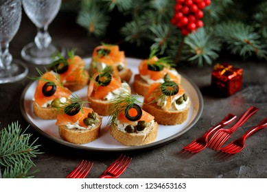 Canapes with cream cheese, salted salmon, capers, olives and dill.
