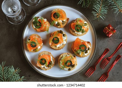 Canapes with cream cheese, salted salmon, capers, olives and dill. Top view.