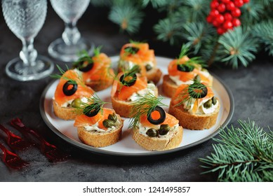 Canapes with cream cheese, salted salmon, capers, olives and dill. Christmas background.