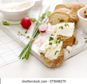 Canapes with curd cheese and fresh chive on a white table. Delicious and healthy breakfast Canapes with curd cheese and fresh chive on a white table