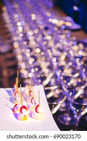 Canapes displayed against a table of glasses at a corporate function.