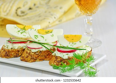 Canapes with goat cheese, red radish, egg slice and dill on white platter