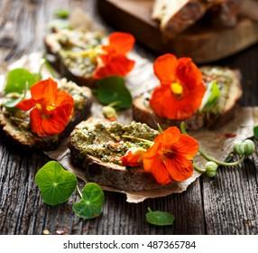 Canapés à l'herbe pesto et fleurs comestibles de capucine