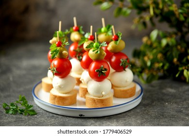 Canapes of mozzarella, green olives, cherry tomatoes, parsley on croutons of white bread.