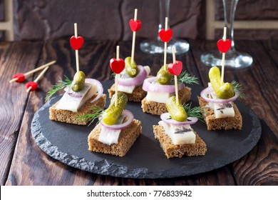 Canapes with rye bread, herring and pickles on a festive table. Valentine's day concept or wedding.