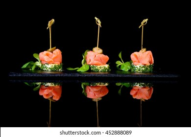 canapes with salmon and capers on black background