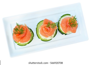 Canapes with smoked salmon, cream cheese and cucumber on white plate isolated on white background, overhead view