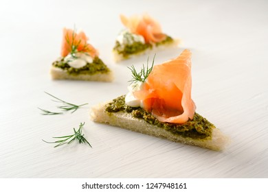 canapes with smoked salmon, pesto, cream and dill garnish on a light background with copy space, selected focus, narrow depth of field