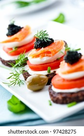 Canapes with smoked salmon, soft cheese, eggs, tomato, caviar and fresh basil. Symbolic image. Concept for a tasty and healthy meal. Food background. Bright background. Close up.