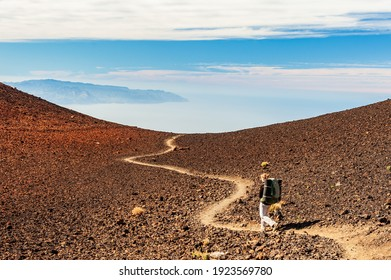 Canary Island La Gomera in sea and young woman hiker with backpack descending from Pico del Teide mountain in El Teide National park. Tenerife, Canary Islands, Spain