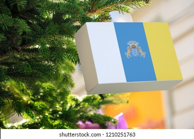 Canary Islands flag printed on a Christmas gift box. Printed present box decorations on a Xmas tree branch. Christmas shopping in Tenerife, Lanzarote, Gran Canaria , sale and deals concept.