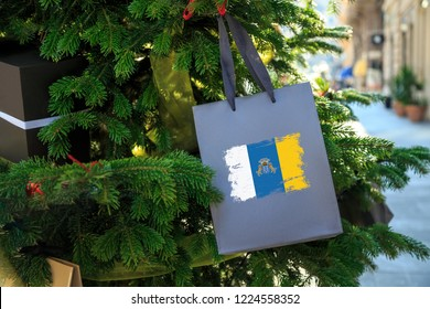 Canary Islands flag printed on a Christmas shopping bag. Close up of a gift bag as a decoration on a Xmas tree on a street. New Year or Christmas shopping, local market sale and deals concept.