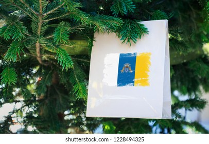 Canary Islands flag printed on a Christmas shopping bag. Close up of a shopping bag as a decoration on a Xmas tree on a street. New Year or Christmas shopping, local market sale and deals concept.