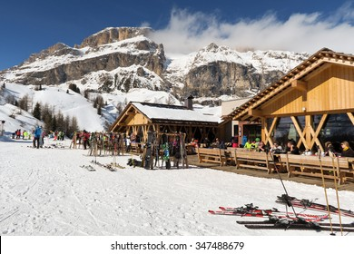 Canazei, Italy - February 23: Skier taking a break at a restaurant a cold sunny day in Canazei ski resort with Italian Dolomites in the background on February 23, 2015 in Canazei, Italy.