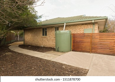 CANBERRA, AUSTRALIA – AUGUST 22, 2018: Side view of a single storey modern brick home with an outside rainwater tank