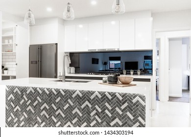 CANBERRA, AUSTRALIA – JUNE 2, 2018: New kitchen furnished with stainless steel fridge, reflective splashback, island, inset sink and three hanging lights in a modern home