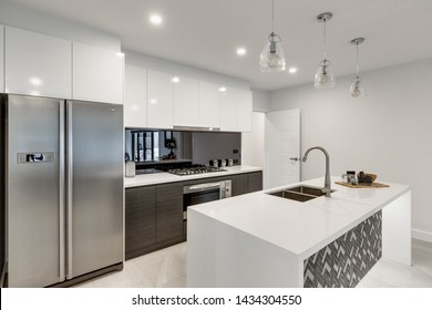 CANBERRA, AUSTRALIA – JUNE 2, 2018: New kitchen furnished with stainless steel fridge, reflective splashback, island, inset sink, stove, oven and three hanging lights in a modern home