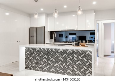 CANBERRA, AUSTRALIA – JUNE 2, 2018: New kitchen furnished with stainless steel fridge, reflective splashback, island, inset sink and three lit hanging lights in a modern home