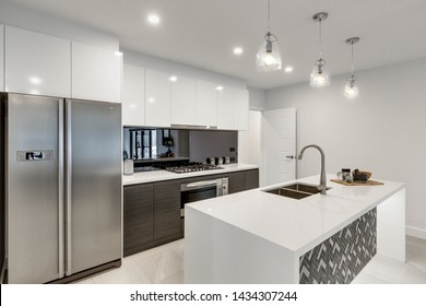 CANBERRA, AUSTRALIA – JUNE 2, 2018: New kitchen furnished with stainless steel fridge, reflective splashback, island, inset sink, stove, oven and three lit hanging lights in a modern home