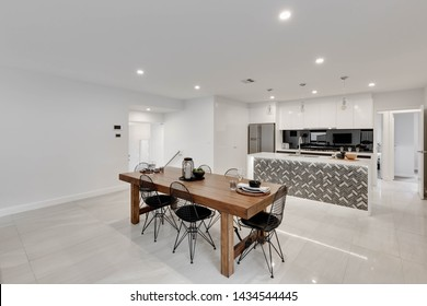 CANBERRA, AUSTRALIA – JUNE 2, 2018: View of a set dining table and chairs with the kitchen behind in a modern home