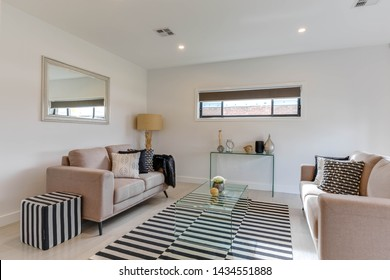 CANBERRA, AUSTRALIA – JUNE 2, 2018: Twin two seater lounges, glass tables, large corner lamp, wall mirror, zebra mat and matching footrest in a sunroom of a modern home