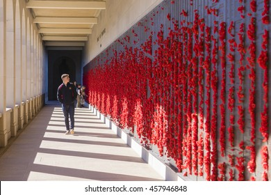 Canberra, Australia - June 29, 2016: View of teenager looking at bronze plaques with names of many Australians who were killed in wars or conflict operations in the Australian War Memorial.