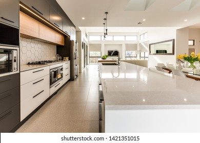 CANBERRA, AUSTRALIA – JUNE 6, 2018: Spacious kitchen furnished with chairs, table, stools, sink, island and large fridge extending into the lounge room in a modern home
