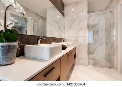 CANBERRA, AUSTRALIA – JUNE 6, 2018: En suite featuring basins, large mirror, cabinet and shower in a modern home