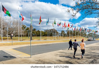 """Canberra, Australia - Sep 3, 2018: """"Avenue of Flags"""" along Queen Elizabeth Terrace near Lake Burley Griffin. People walking and jogging in the foreground as a recreational pursuit."""