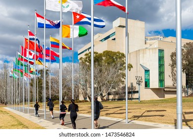 """Canberra, Australia - Sep 3, 2018: """"Avenue of Flags"""" along Queen Elizabeth Terrace. The High Court of Australia building in the background (to the right). Joggers run pass on a pedestrian pathway."""