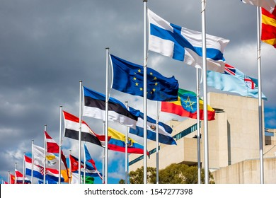 """Canberra, Australia - Sep 3, 2018: Low angle view of the """"Avenue of Flags"""" along Queen Elizabeth Terrace. The High Court of Australia building in the background. Storm clouds approaching."""