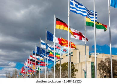 """Canberra, Australia - Sep 3, 2018: Street view of the """"Avenue of Flags"""" along Queen Elizabeth Terrace. The High Court of Australia building in the background. Storm clouds approaching."""