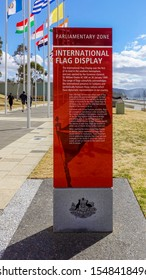 """Canberra, Australia - Sep 3, 2018: Information sign to the """"Avenue of Flags"""" at the Parliamentary Zone along Queen Elizabeth Terrace. A few joggers pass by in the background."""