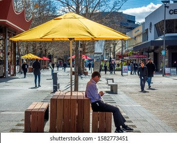 Canberra, Australia - Sep 3, 2018: Public bench with bright yellow umbrella to shelter from the harsh sunlight in Canberra Center shopping mall. People around. Man on the bench using his cellphone.