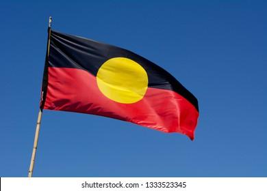 CANBERRA - FEB 24 2019:The Australian Aboriginal Flag wave against blue sky in Australia. The Australian Aboriginal Flag represents Aboriginal Australians native people