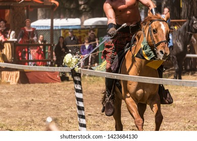 Canby, Oregon - June 9, 2019: Medieval Knight on horseback slashing cabbage with a sword in jousting competition at a Reconnaissance Fair.