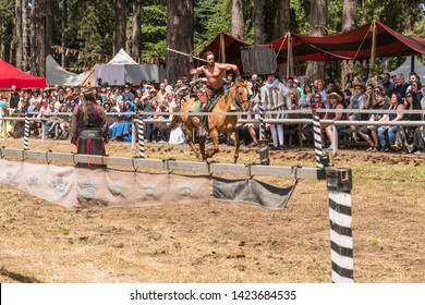 Canby, Oregon - June 9, 2019: Medieval Knight on horseback throwing a spear at a target in jousting competition at a Reconnaissance Fair.