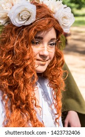 Canby, Oregon - June 9, 2019: Woman with red hair dressed in colorful costume at a Renaissance Fair.