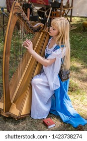 Canby, Oregon - June 9, 2019: Beautiful blond woman dressed in renaissance period clothing playing a harp at a renaissance fair.
