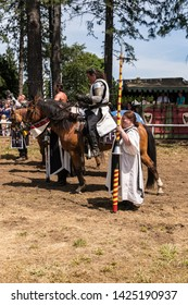 Canby, Oregon - June 9, 2019: Medieval Knight on horseback entering castle grounds in jousting competition at a Reconnaissance Fair.