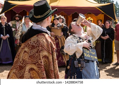 Canby, Oregon - June 9, 2019: Woman drinking from ancient pewter mug wearing medieval style clothing, dress at a renaissance fair.