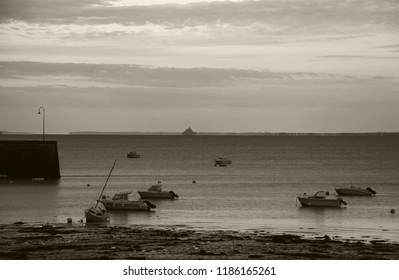 Cancale (Brittany) at sunset. Mooring sailing boats and view of dreamy silhouette of Mont Saint Michel at horizon. Sepia photo.